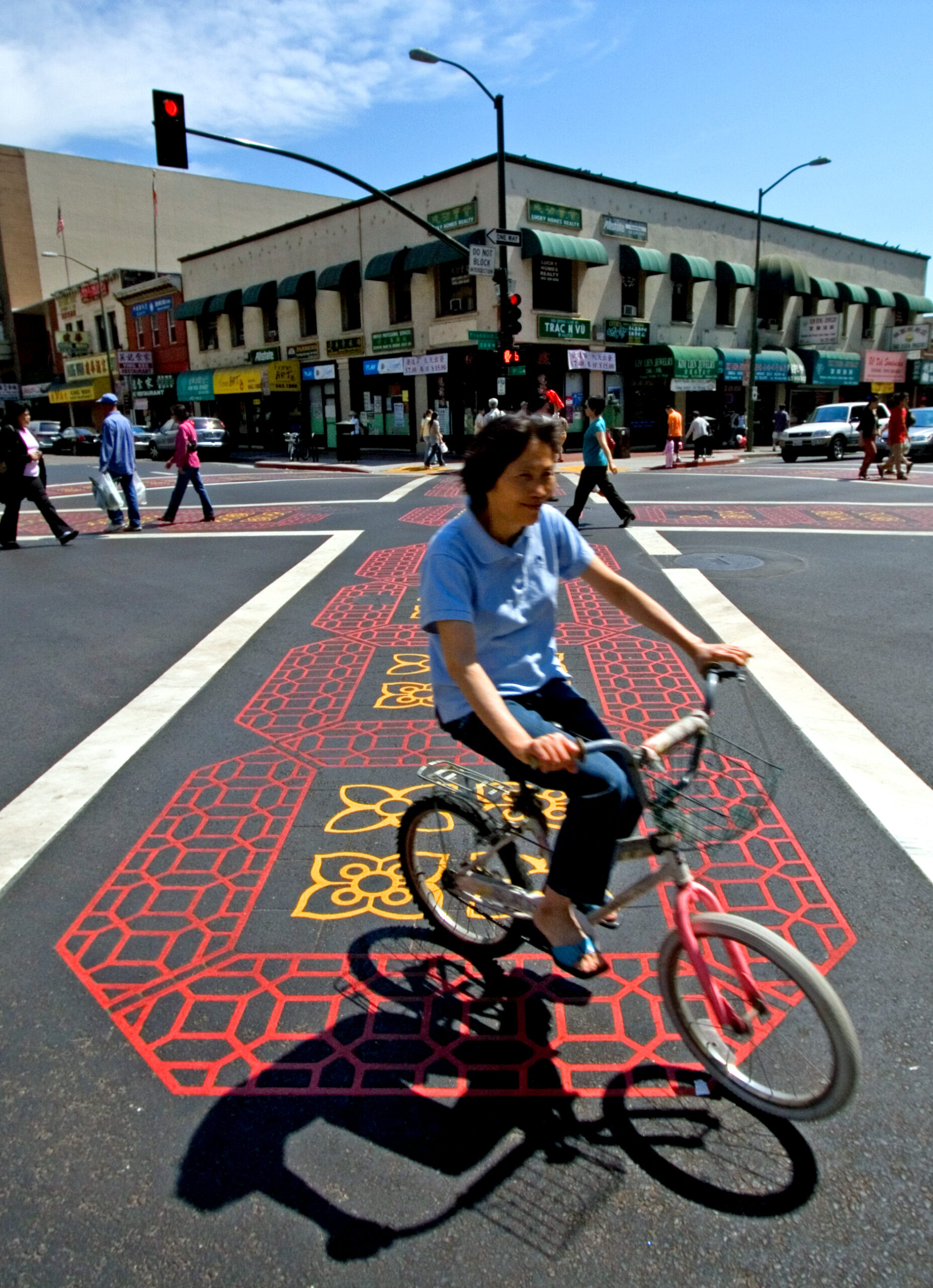 an asian woman on a bike rolling through a decorative crosswalk in chinatown/Oakland