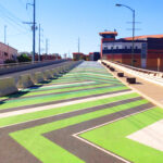 Image of Downtown Pathways pedestrian walkway in El Paso. The path is painted in green and white chevron.