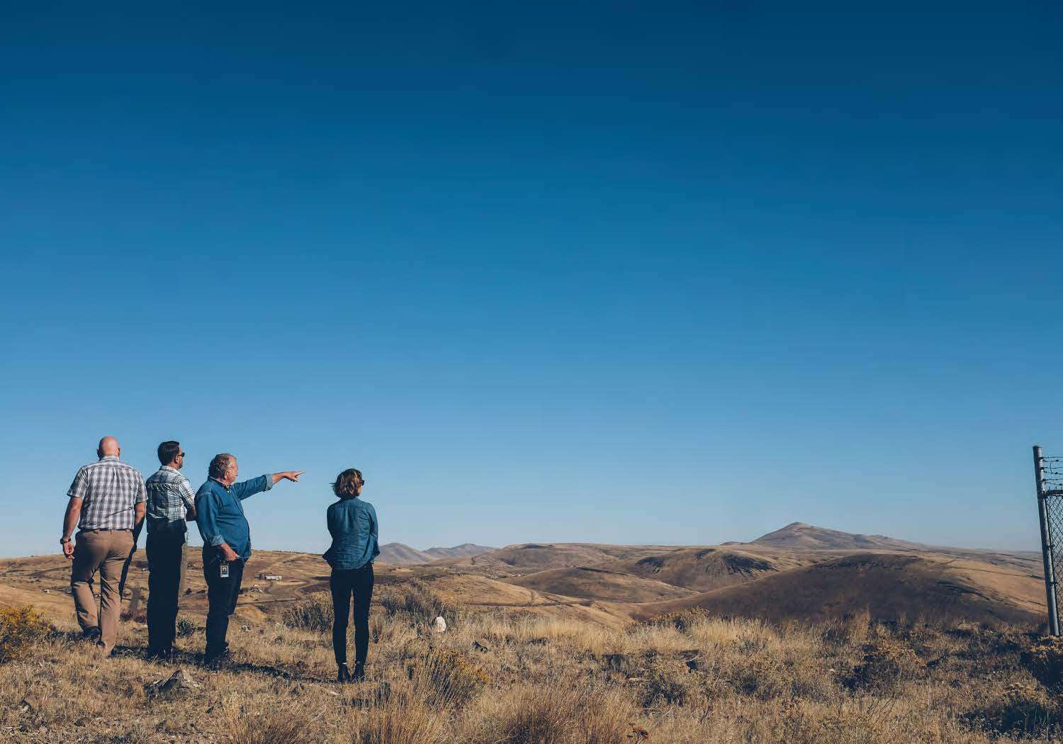 artists with dot staff on open plains pointing away at mountains