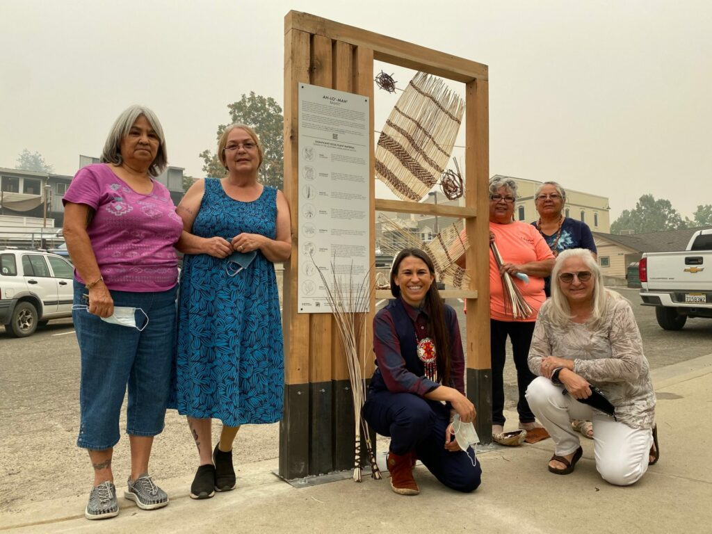 Photo of women standing around and beside their outdoor engagement installation
